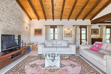 Bright and cozy living room with wooden ceiling and beams in villa Karojba