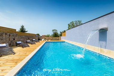 Private pool with pool massage waterfall curtain and rustic wooden sun loungers with towels in charming villa