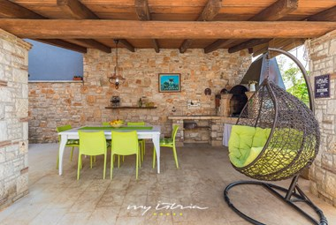 Summer kitchen with dining area and elegant egg chair swing in charming villa