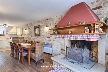 Bright kitchen and dining area by a fireplace in traditional Istrian style in Villa San Rocco in Vodnjan