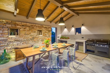 Outdoor dining area with a summer kitchen and barbecue in villa near Pula