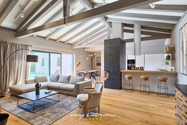 Open space concept living area with fireplace and high beam ceilings in Villa Grotte