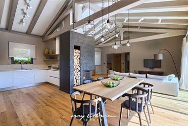 Bright open space concept kitchen, dining and living area with modern fireplace and high ceilings with wooden beams in Villa Grotte