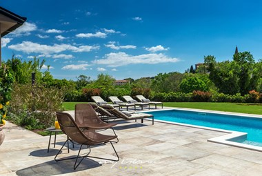 Outside lounge area and sun loungers by the pool overlooking the magnificent green nature around the villa