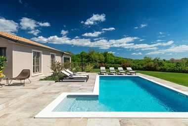 Private swimming pool with sun loungers and a lounge area overlooking the beautiful green garden in rustic and modern villa Grotte