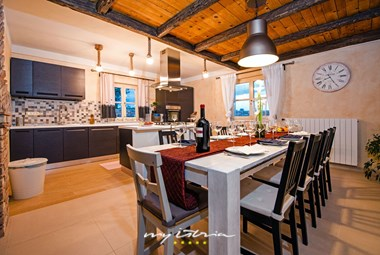 The kitchen in Villa Tomani is connected to the dining area and the living room