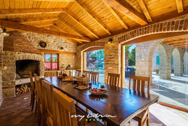 Beautiful open lounge, dining and kitchen area with rustic furniture and fireplace on the ground floor of the villa