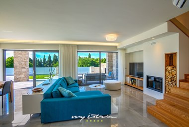 Villa´s beautifully decorated living room with large windows and access to the pool
