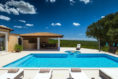 Beautiful pool and cosy sun loungers in front of the villa