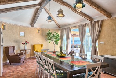 Bright dining area with rustic details and access to the garden of the villa