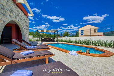 Inviting pool area in Villa Vacanza with relaxing sun loungers