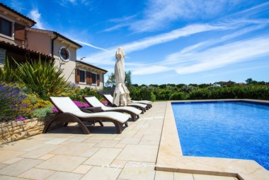 Sun loungers next to the pool in our villa in Pula