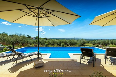 The villa has a private pool with sun loungers and sun umbrellas