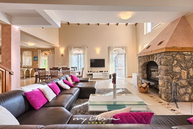 Cosy living room with a large fireplace that enables warm atmosphere in the villa