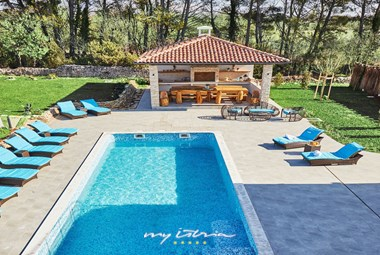 The relaxing pool terrace in Villa Prestige with a covered outside dining area, including a a traditional open fireplace