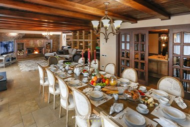 The impressive dining room in Villa Richi with large, gallery-like patio doors opening on the pool terrace