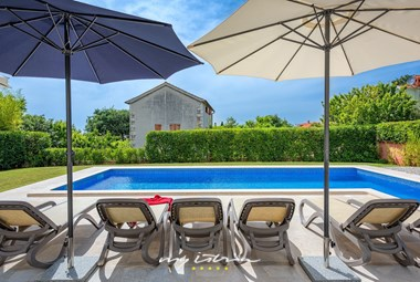 Cosy sun loungers next to villa´s pool