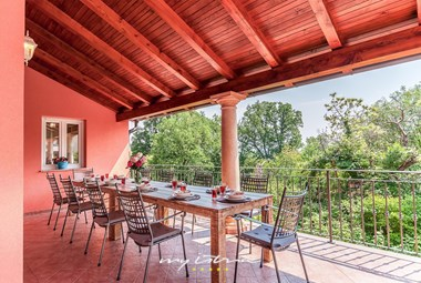 Large dining table on villa´s terrace in natural surrounding