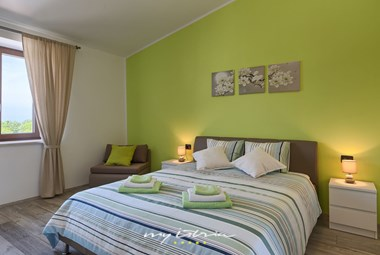 Comfortable bedroom with double bed in Villa Melani