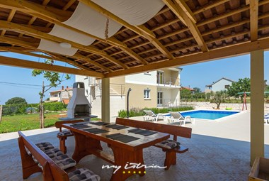 Covered outdoor dining area with BBQ and pool view in Villa Renata