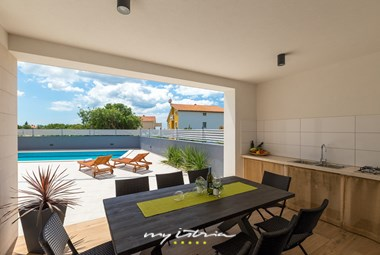 Covered outdoor dining area with kitchen in Villa Pergosa
