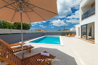 Relax on the sun loungers next to the lovely pool in this elegant villa!