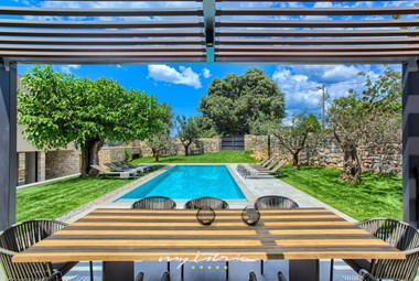 Outdoor dining area with view over the pool area in Villa Melon