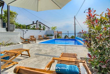 Enjoy sun-bathing next to the lovely pool with a sea view at Villa Leticija