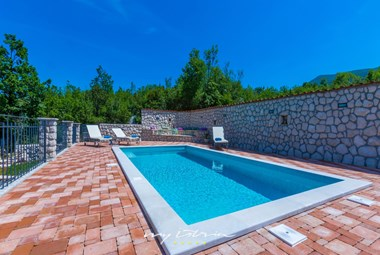 The inviting pool in our holiday villa in Dalmatia is surrounded by a beautiful paved terrace