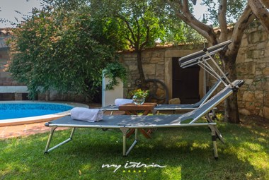 Comfortable sun loungers in the shade next to the pool in Villa Edi
