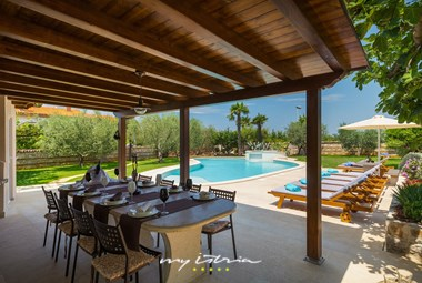 The villa has a covered terrace with an outdoor kitchen and dining area