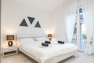 Bright bedroom with balcony doors and direct pool access in Villa La Vita