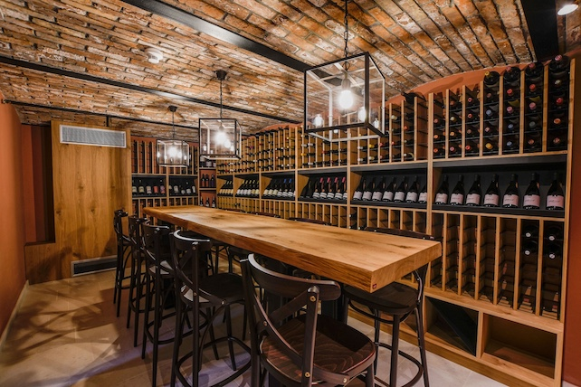 wine-cellar-at-villa-stancija-baracija-with-a-wooden-table-and-many-wine-bottles-on-shelves