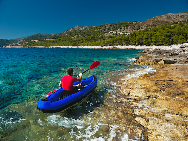 A man with paddle in a blue kayak near the rocky green wooded coast with hills
