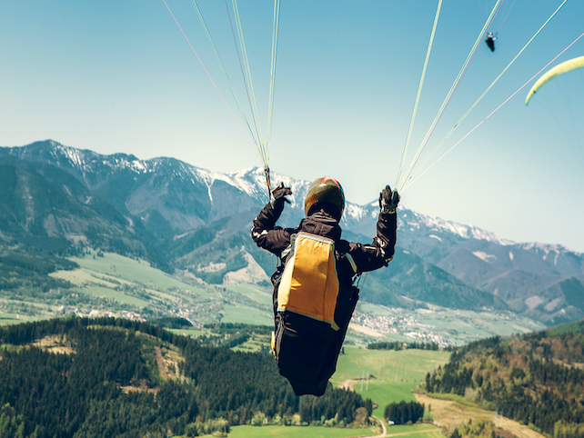 A man is hanging in the air on a paraglider above green landscape and mountains