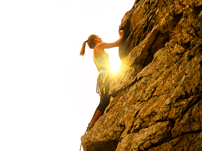 A woman with climbing equipment is climbing up a steep cliff with sun behind