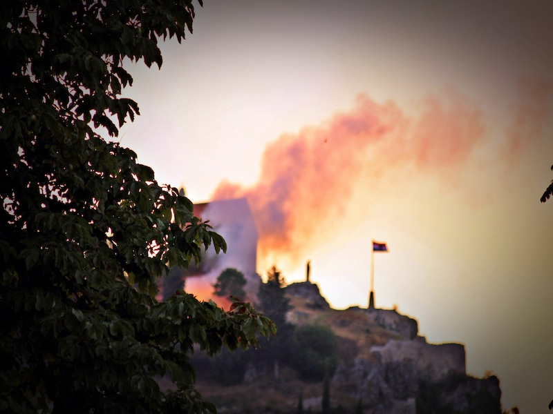 The remains of the old fortress and burning fire over the city of Sinj