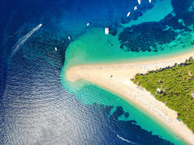 view-from-above-of-sandy-beach-zlatni-rat-in-the-shape-of-a-triangle-surrounded-by-sea
