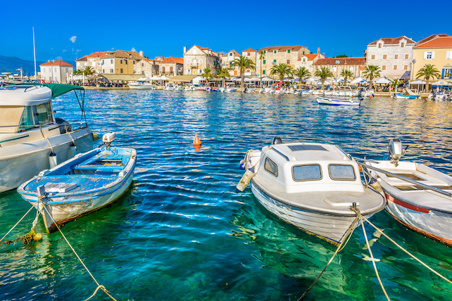 small-wooden-boats-tied-in-a-dock-on-Brac-with-houses-in-the-background