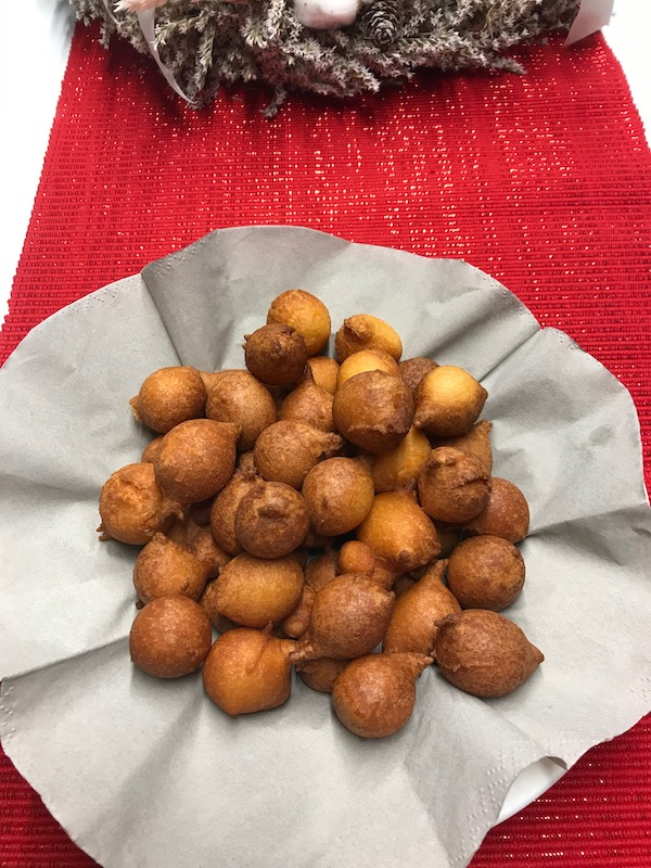 traditional-round-sweets-called-fritule-on-a-white-plate-and-layed-out-on-red-table