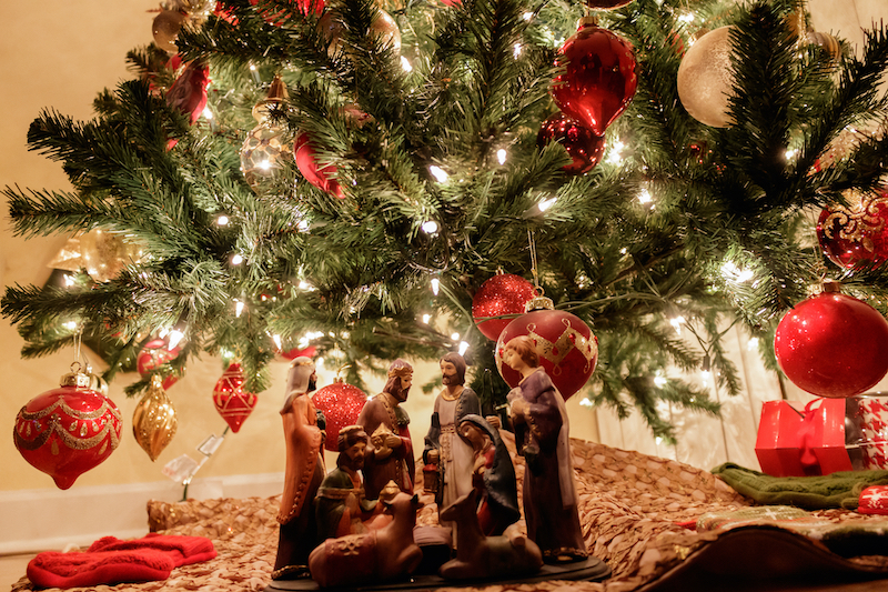 figurines-of-Mary-Joseph-and-baby-Jesus-in-a-nativity-scene-underneath-christmas-tree