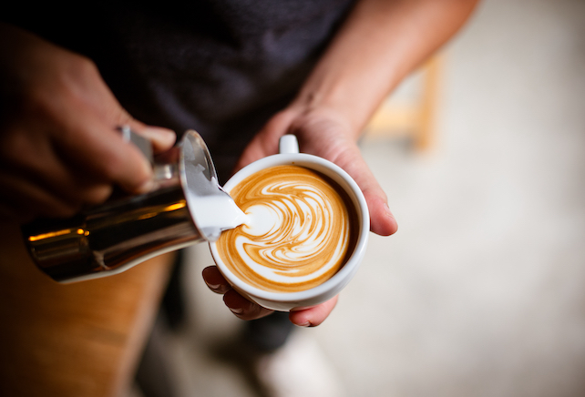 barista-pouring-foamy-milk-into-coffee-cup-creating-a-beautiful-pattern