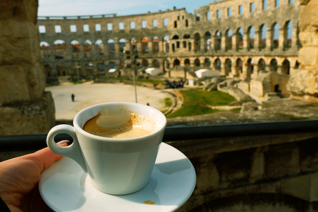 woman´s hand holding a small coffee cup with a view of the Arena in Pula