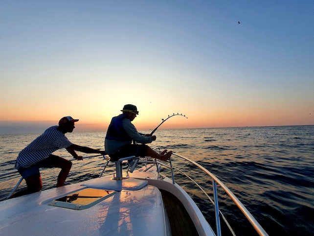 two-fishermen-on-a-boat-with-a-fishing-rod-enjoying-fishing-while-the-sun-is-down
