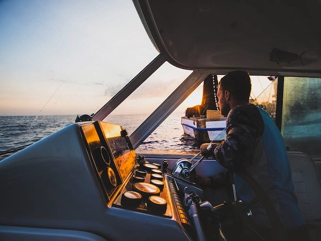 captain-of-a-fishing-boat-navigating-during-sunset-on-open-sea