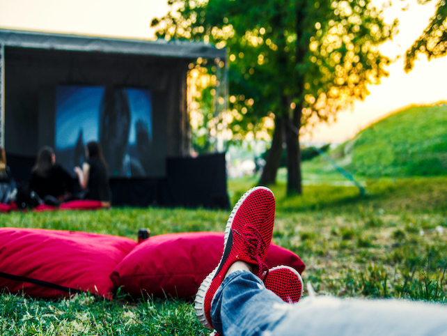 Person stretching out on the green grass under the clear sky and enjoy the movie
