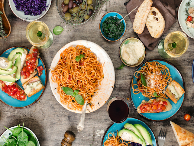 pasta plates, bread, sauce and olives in bowls and 3 glasses of wine on table