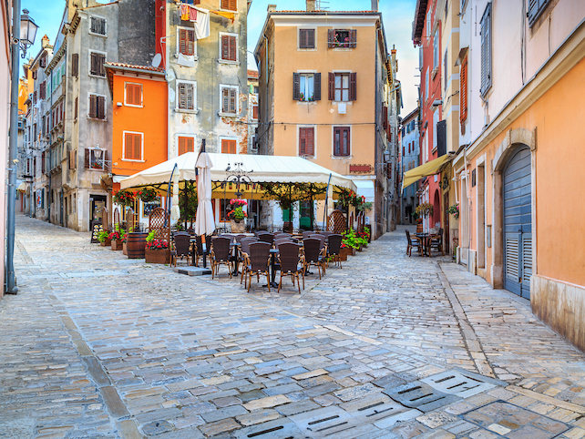 terrace of cafe, chairs, tables and pavillion amongst colorful houses in Rovinj
