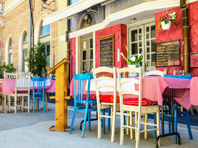 chairs and tables in front of restaurant and chalk written menu on red facade