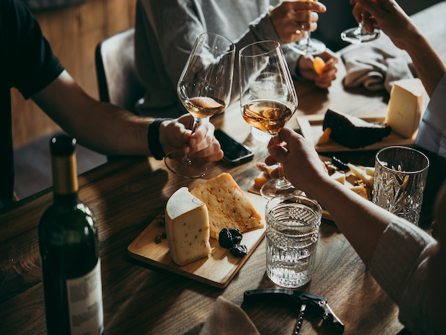 hands with white wine at clinking and cheese, glasses and bottle on the table